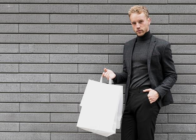 Mann mit einer hand in seiner tasche, die zur kamera schaut Kostenlose Fotos