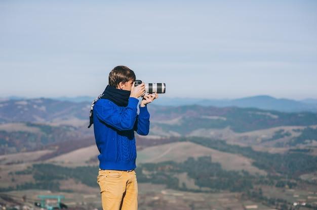 Mann mit einer kamera am rand einer klippe, welche die berge unten übersieht Premium Fotos
