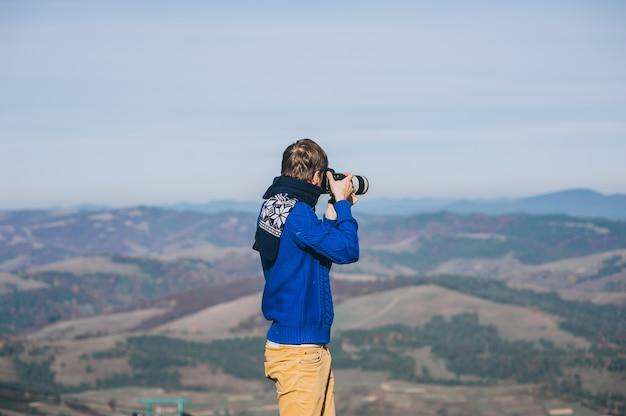 Mann mit einer kamera am rande einer klippe mit blick auf die berge Premium Fotos