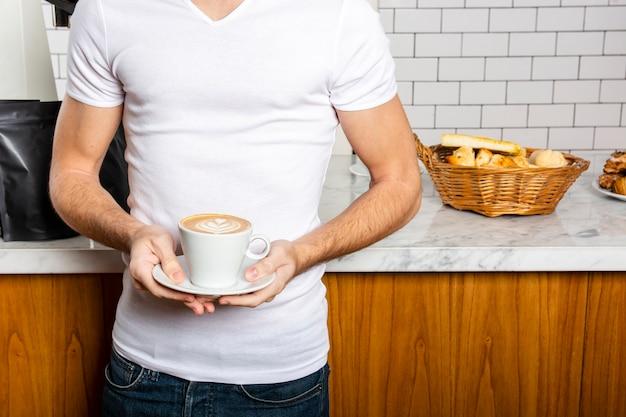 Mann mit einer tasse cappuccino in seinen händen Kostenlose Fotos