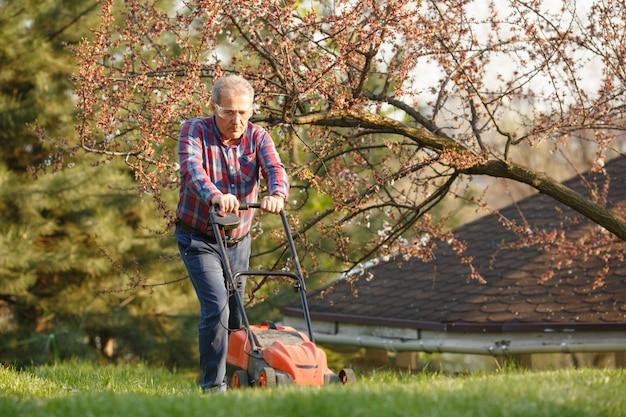 Mann mit elektrischem rasenmäher, rasenmähen. gärtner, der einen garten trimmt. sonniger tag, vorort, dorf. erwachsener mann, der garten beschneidet und landschaftlich gestaltet, gras, rasen, wege trimmend. harte arbeit an der natur. Premium Fotos
