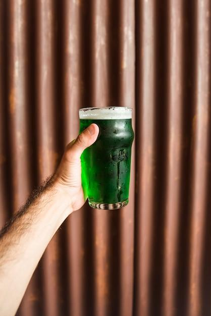 Mann mit glas grünes getränk nahe hölzerner wand Kostenlose Fotos