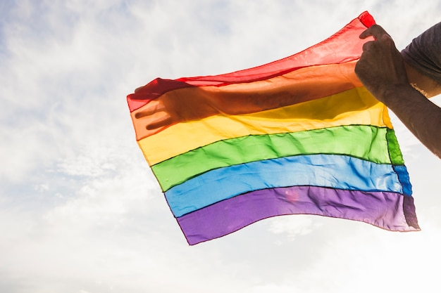 Mann mit großer flagge in lgbt-farben und blauem himmel mit sonnenschein Kostenlose Fotos