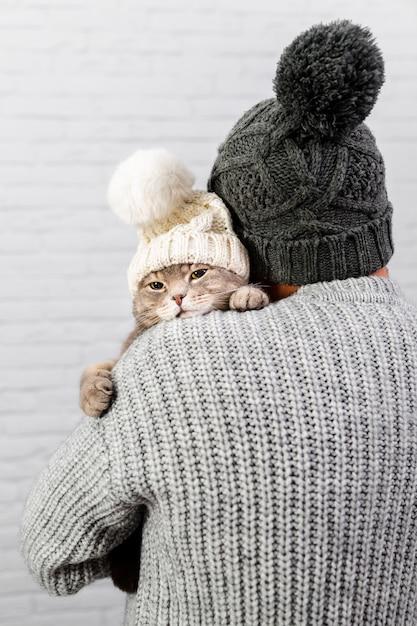 Mann mit hinterer haltener katze mit pelzmütze Kostenlose Fotos