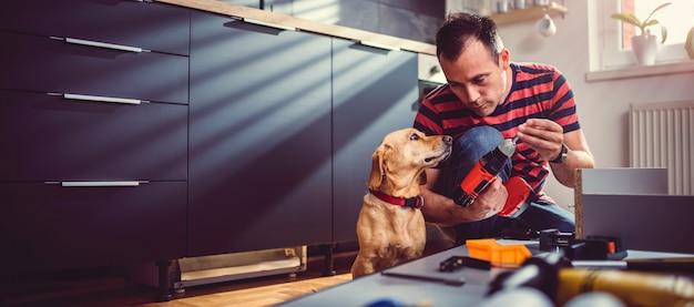 Mann mit hund, der küchenschränke errichtet Premium Fotos