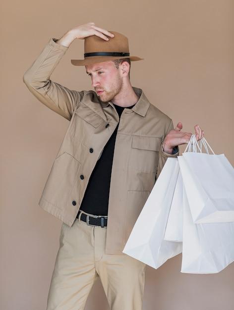 Mann mit hut auf kopf und einkaufstüten Kostenlose Fotos