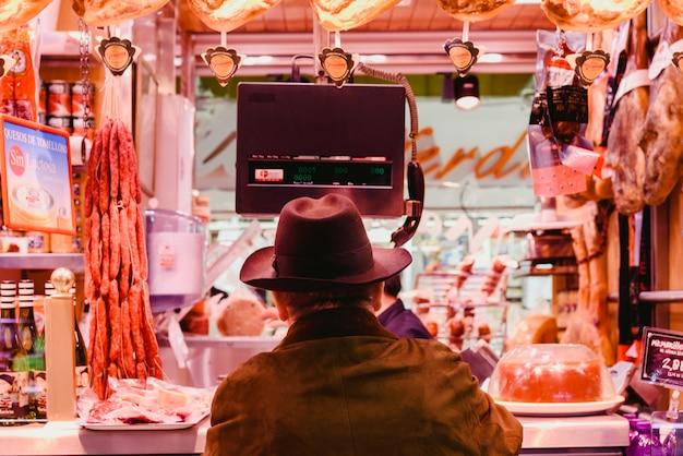 Mann mit kaufender wurst des hutes in einer metzgerei. Premium Fotos