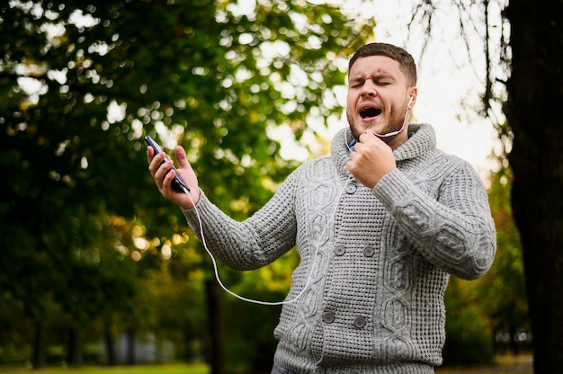 Mann mit kopfhörern in den ohren singend im park Kostenlose Fotos