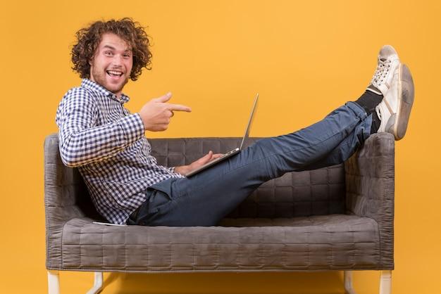 Mann mit laptop auf der couch Kostenlose Fotos