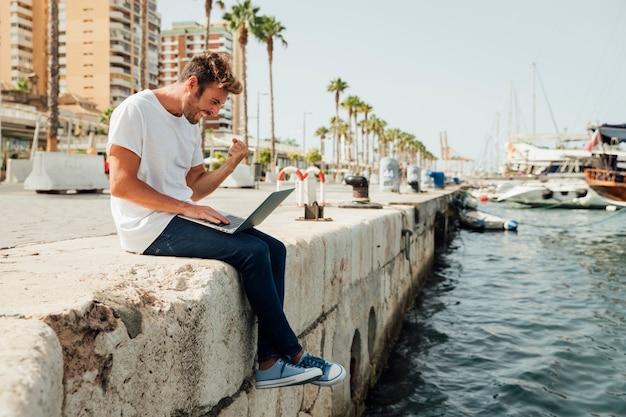 Mann mit laptop feiert am fluss Kostenlose Fotos