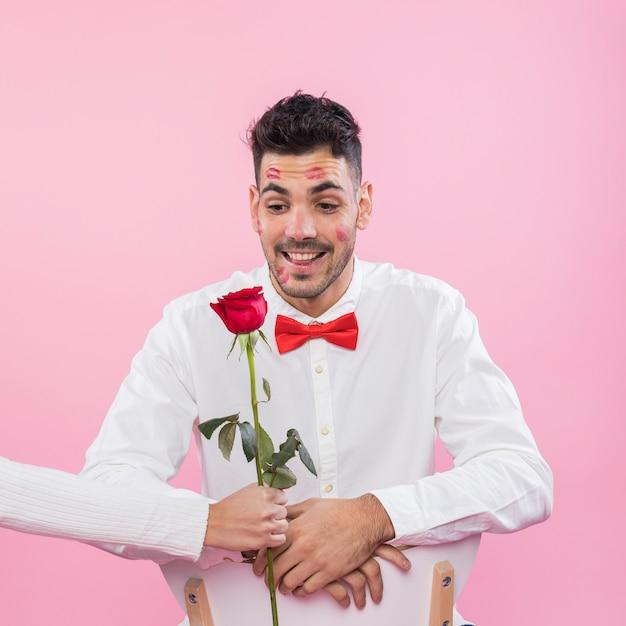 Mann mit lippenstiftkusskennzeichen auf dem betrachtenden gesicht stieg Kostenlose Fotos