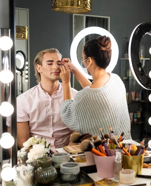 Mann mit make-up und frau helfen ihm Kostenlose Fotos