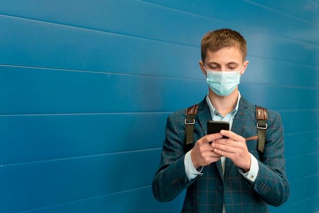 Mann mit medizinischer maske und rucksack unter verwendung des smartphones Premium Fotos