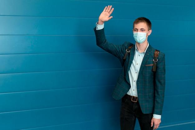 Mann mit medizinischer maske und winkendem rucksack Premium Fotos