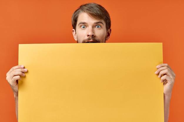 Mann mit orange blatt papier poster modell marketing isoliert hintergrund. hochwertiges foto Premium Fotos