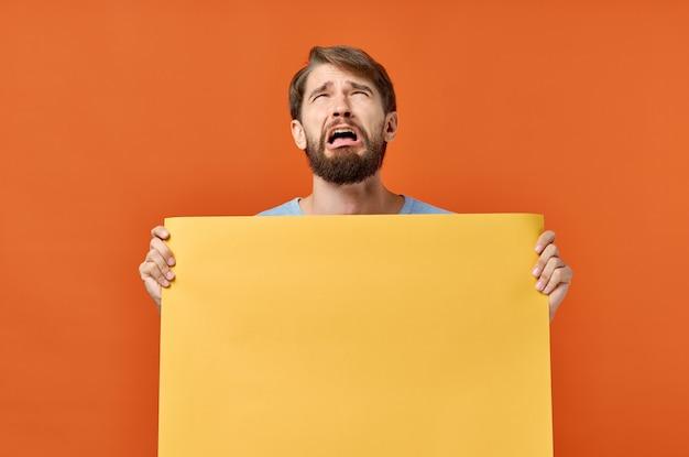 Mann mit orange blatt papier poster modell marketing isoliert. Premium Fotos