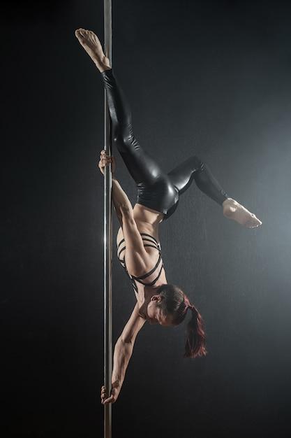 Mann mit pylon. männliches stangentänzertanzen auf einem schwarzen hintergrund Premium Fotos