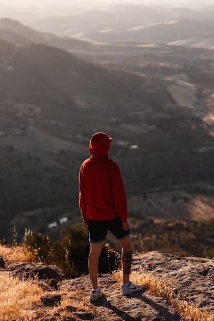 Mann mit rotem sweatshirt mit unscharfer landschaft Premium Fotos