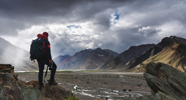 Mann mit rucksack, der die kamera steht auf klippe mit mountain view und sonnenlicht durch wolke hält. Premium Fotos