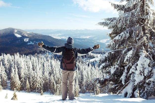 Mann mit rucksack trekking in den bergen. kaltes wetter, schnee auf hügeln. winterwandern. der winter kommt, erster schneefall. konzept von reisen, ruhe, entspannung Premium Fotos