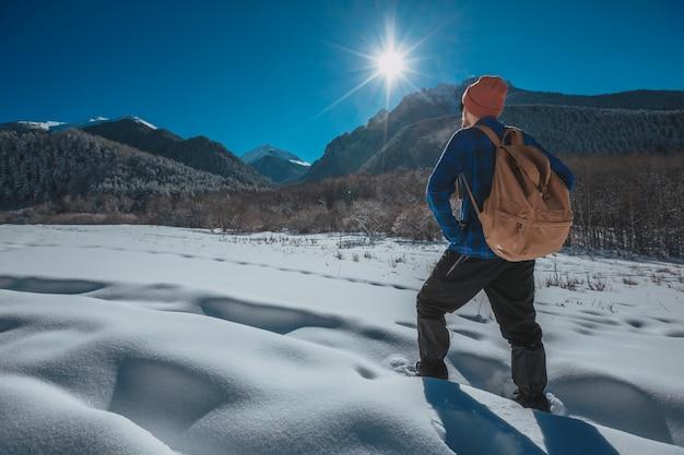 Mann mit rucksack trekking in den bergen. kaltes wetter, schnee auf hügeln. winterwandern. sonne und schnee Premium Fotos