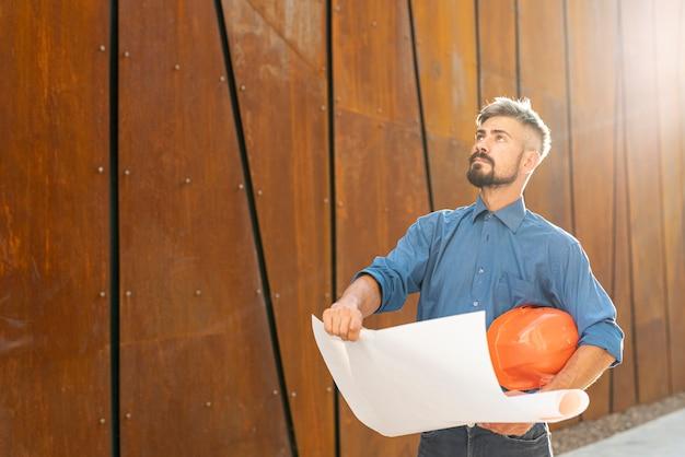 Mann mit schaltplan und helm Kostenlose Fotos