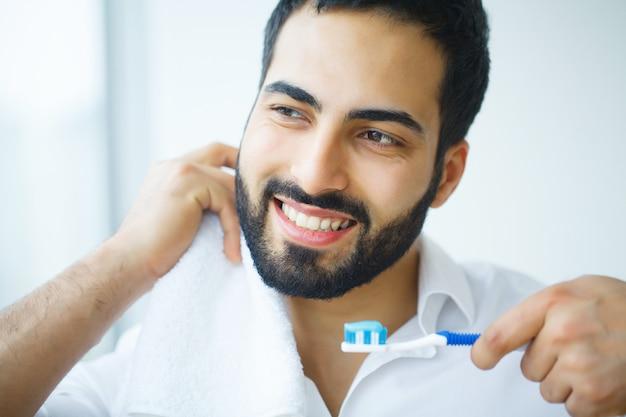 Mann mit schönem lächeln, gesunde weiße zähne mit zahnbürste. Premium Fotos
