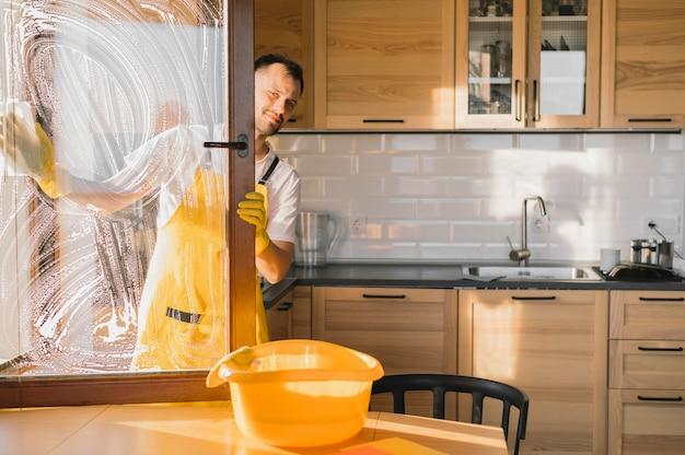 Mann mit schürzenreinigungsfenster Kostenlose Fotos