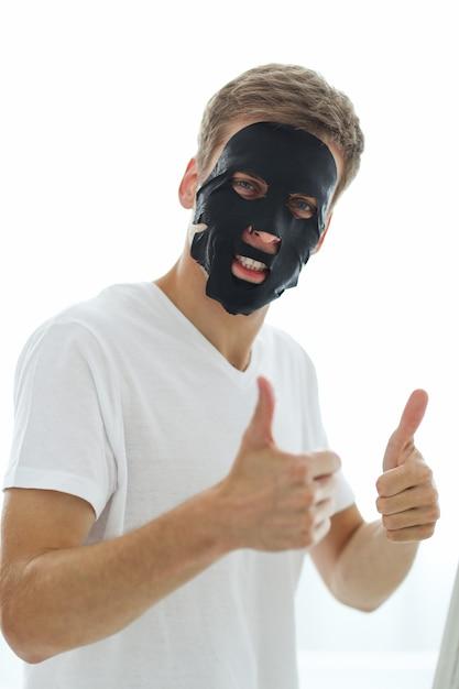 Mann mit schwarzer gesichtsmaske, hautreinigungskohle. schönheitskonzept Kostenlose Fotos
