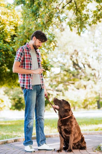 Mann mit seinem hund, der auf gehweg im garten steht Kostenlose Fotos