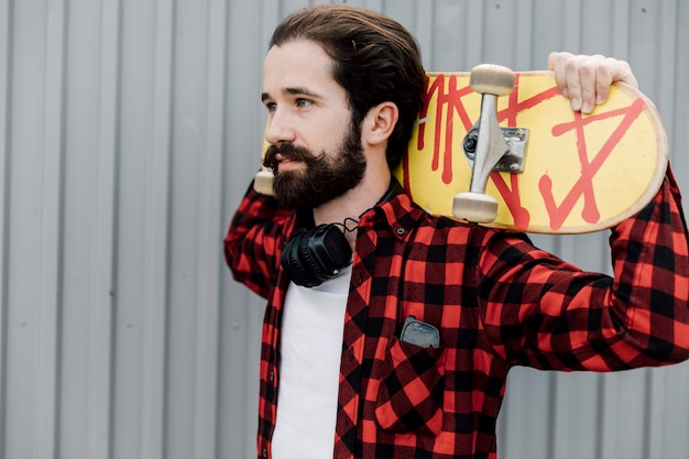 Mann mit skateboard und kopfhörern Kostenlose Fotos