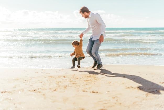 Mann mit springendem kleinkind auf küste Kostenlose Fotos