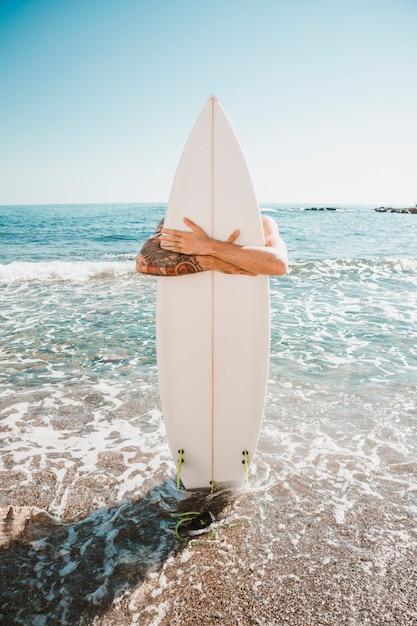 Mann mit surfbrett am strand in der nähe von meer Kostenlose Fotos