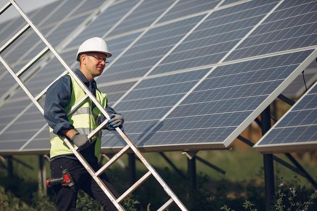 Mann mit weißem sturzhelm nahe einem sonnenkollektor Kostenlose Fotos