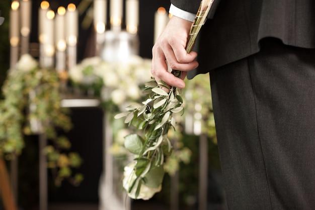 Mann mit weißen rosen bei der beerdigung Premium Fotos
