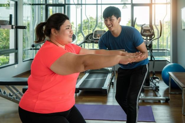Mann mit zwei asiaten und überladenes frauentrainieren dehnen zusammen in die moderne turnhalle aus, glücklich und lächeln während des trainings. fette frauen kümmern sich um gesundheit und möchten gewichtskonzept verlieren. Premium Fotos