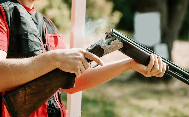 Mann öffnet den schrotflintenbolzen nach einem schuss mit rauch Kostenlose Fotos