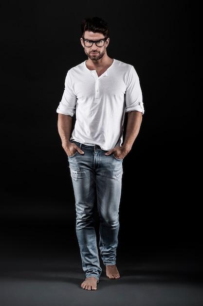 Mann posiert mit brille, jeans und weißem t-shirt Kostenlose Fotos