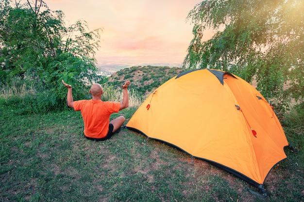 Mann praktiziert yoga nahe einem orangefarbenen zelt auf hügel Premium Fotos