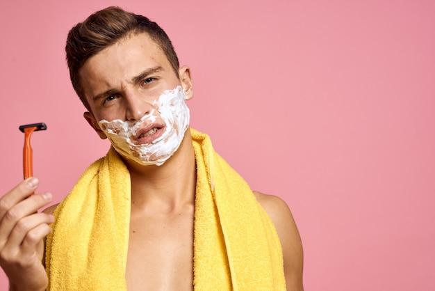 Mann rasiert sein gesicht mit einem rasiermesser mit rasierschaum Premium Fotos
