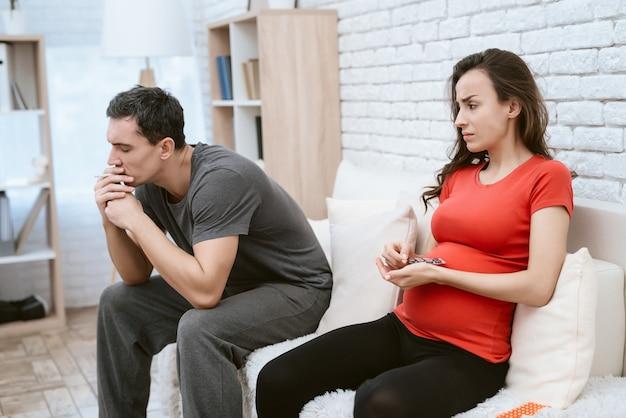 Mann raucht eine zigarette neben sich ist seine schwangere frau. Premium Fotos