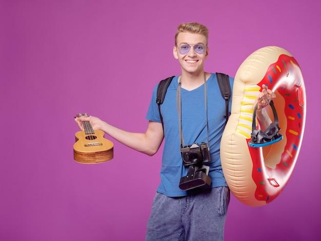 Mann reisender mit kamera, schwimmkreis und gitarrenukulele auf lila hintergrund Premium Fotos