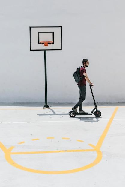Mann reiten e-roller auf einem basketballplatz Kostenlose Fotos