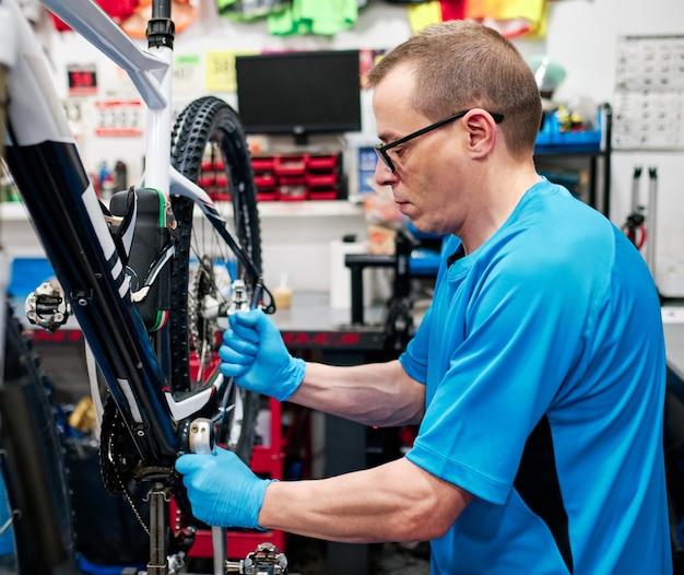 Mann repariert ein fahrrad in seiner kleinen werkstatt Premium Fotos