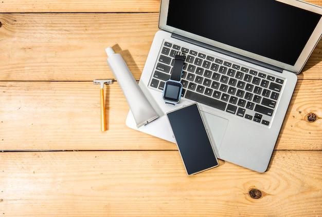 Mann sachen wie laptop, smartwatch, handy, gelber rasierer und zahnpasta produkt für unterwegs Premium Fotos