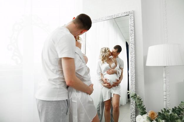 Mann sanft küssen und umarmt schwangere frau in stilvollem interieur. sanfte umarmungen zukünftiger eltern im schlafzimmer vor dem spiegel. glückliche familie, die auf baby wartet. Premium Fotos