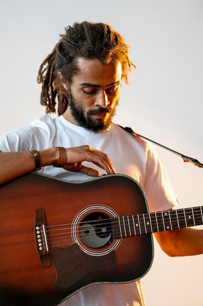 Mann schaut auf seine gitarre hinunter Kostenlose Fotos