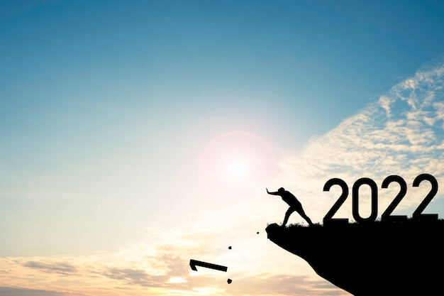 Mann schieben nummer null die klippe hinunter, wo die nummer 2022 mit blauem himmel und sonnenaufgang hat. es ist ein symbol für den beginn und ein willkommenes frohes neues jahr 2022 Premium Fotos