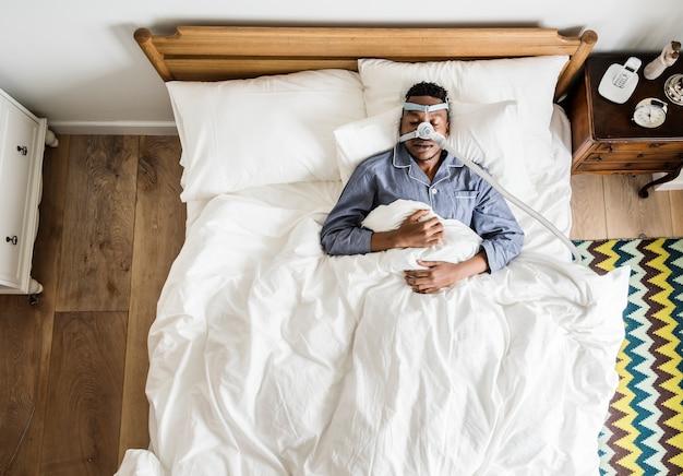 Mann schläft mit einer anti-schnarch-maske   Premium-Foto