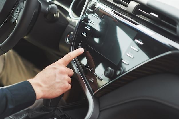 Mann schließt ein audiosystem in das auto ein. Kostenlose Fotos